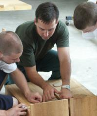 Photograph of DNR's Mike Wilcox and teens building nest boxes.